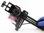 Вид на объектив фотоаппарата, закрепленного в универсальном адаптере для цифровых устройств